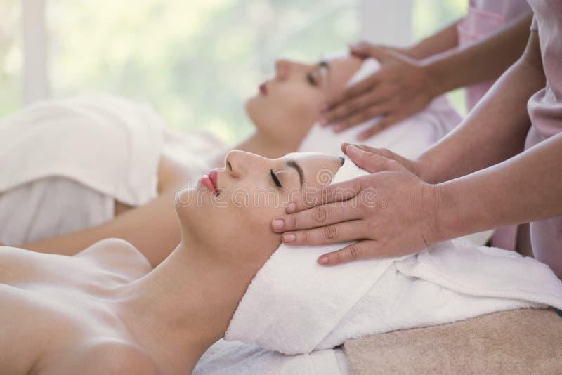 Masajista que hace masaje la cabeza de la mujer joven hermosa que se relaja foto de archivo libre de regalías