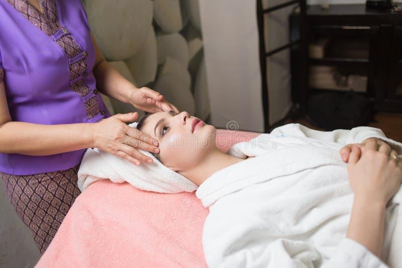 Masajista que hace masaje la cabeza de una mujer caucásica en el salón del balneario fotos de archivo libres de regalías