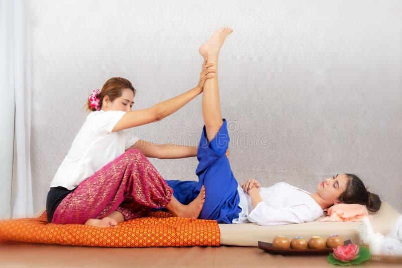 Masajista tailandesa que hace el masaje para la mujer de la forma de vida en salón del balneario Mujer hermosa asiática que consi imagenes de archivo