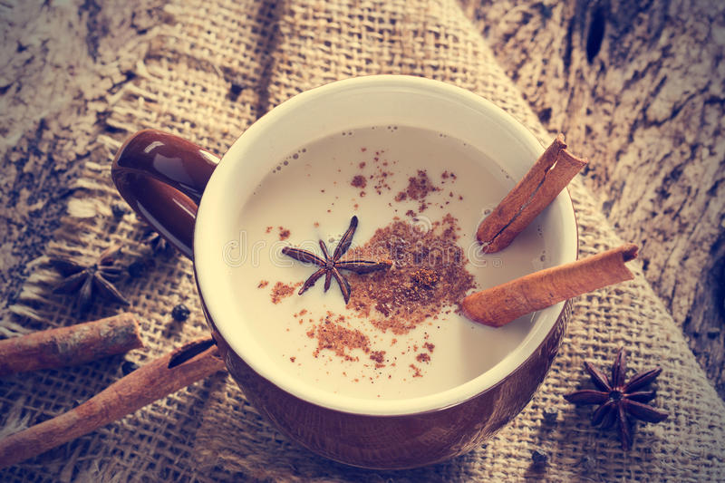 Masala chai tea with spices and star Anise, cinnamon stick, peppercorns, on sack and wooden background. Masala chai tea with spices and star Anise, cinnamon stock photo