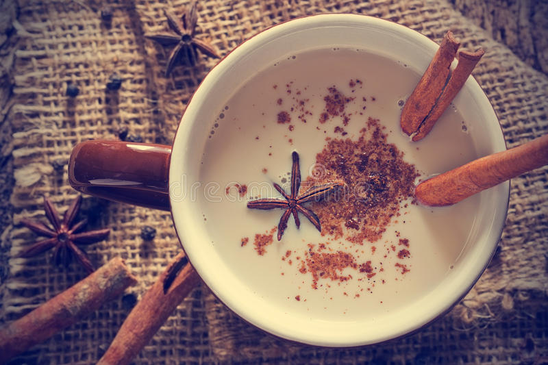 Masala chai tea with spices and star Anise, cinnamon stick, peppercorns. On sack and wooden background royalty free stock photography