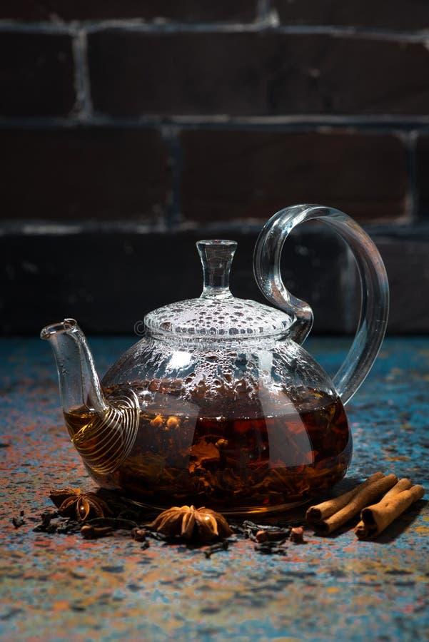 Masala del té en una tetera de cristal en un fondo oscuro, vertical foto de archivo