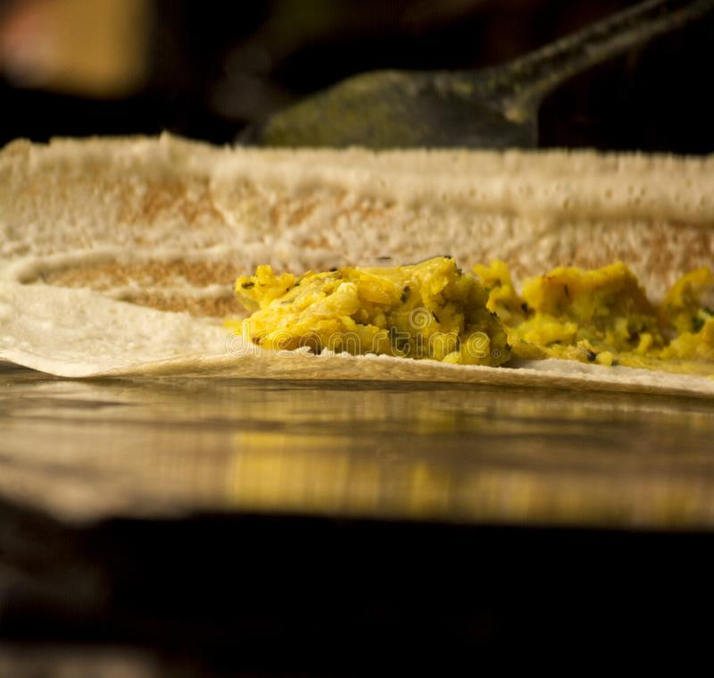 Masala dosa on a frying pan filled with potatoes royalty free stock images