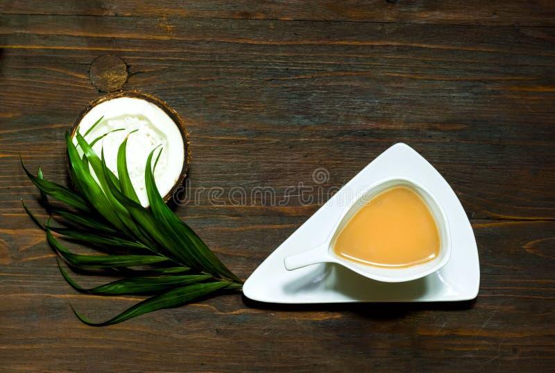 Masala het helen thee met kokosmelk in witte uitstekende kop op houten achtergrond, het concept van het veganistrecept, exemplaar stock foto's