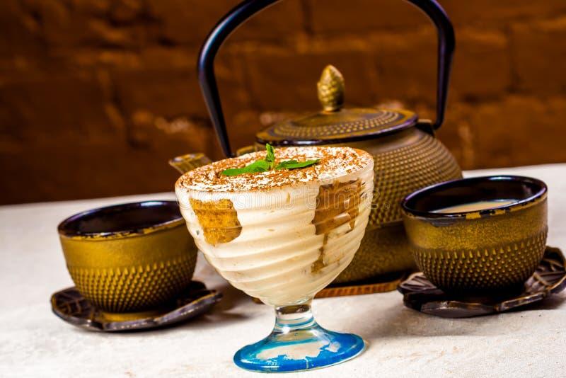 Masala indien Chai, thé au lait épicé Théière et tiramisu photo stock