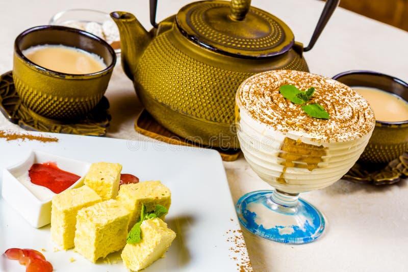 Masala indio chai, té con leche condimentado Tetera y dulces imagen de archivo libre de regalías