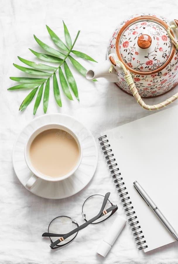 Masala te, tekanna, notepad, exponeringsglas, penna, grönt blommablad på vit bakgrund, bästa sikt Morgoninspirationplanläggning fotografering för bildbyråer