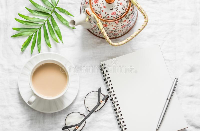 Masala tea, teapot, notepad, glasses, pen, green flower leaf on white background, top view. Morning inspiration planning. royalty free stock photo