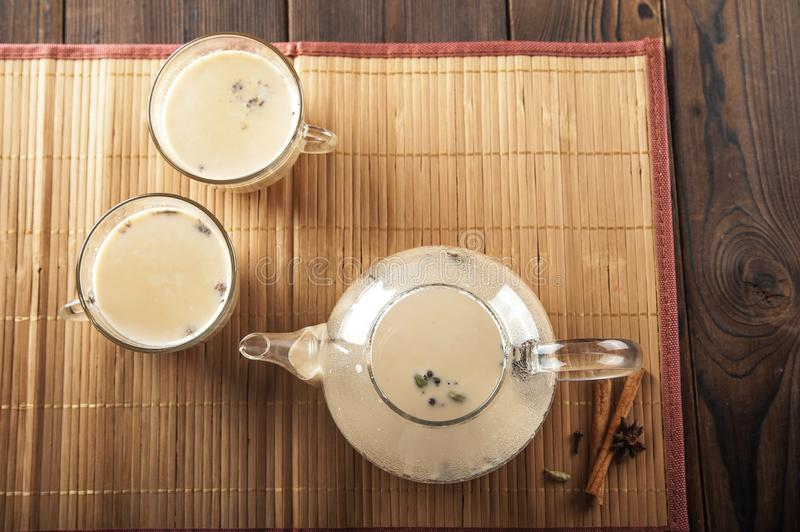 Masala tea on a textural wooden background. A teapot is a transparent tea pot with mugs and Indian national tea masala. Milk, ging. Er, cardamom, cloves, nutmeg stock photography