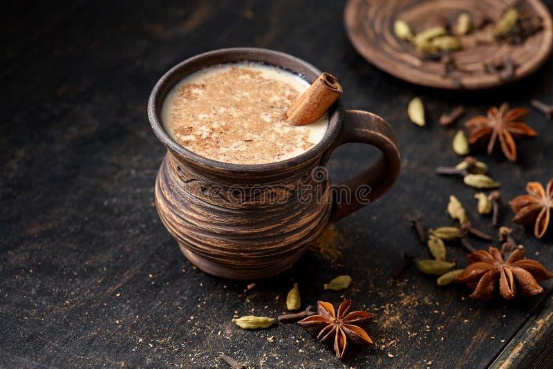 Masala a tiré la boisson épicée indienne chaude de lait doux de latte de Chai de thé, gingembre, épices fraîches et les herbes se photo stock