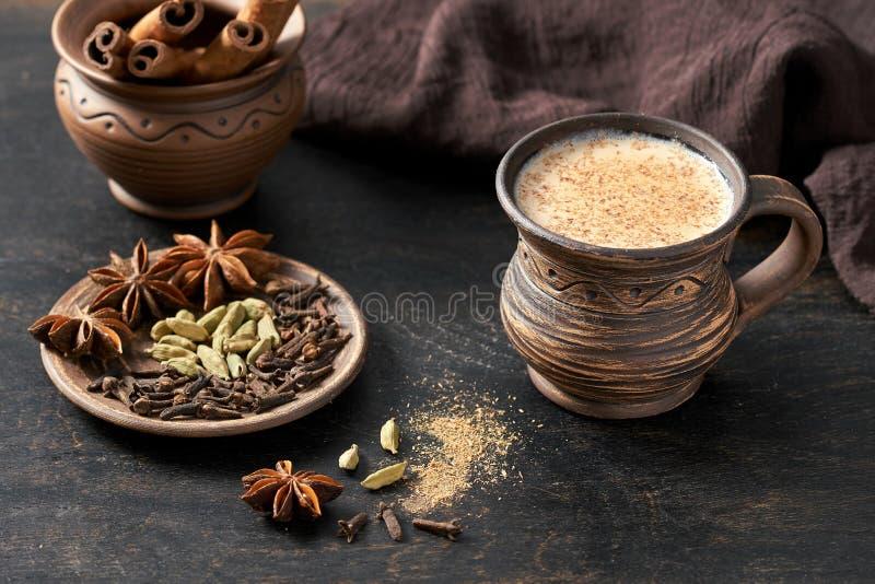 Masala zog heißes indisches gewürztes Getränk der süßen Milch Teechai-Latte, Zimtstange, Nelken, frische Gewürze und Kräuter misc stockfotografie
