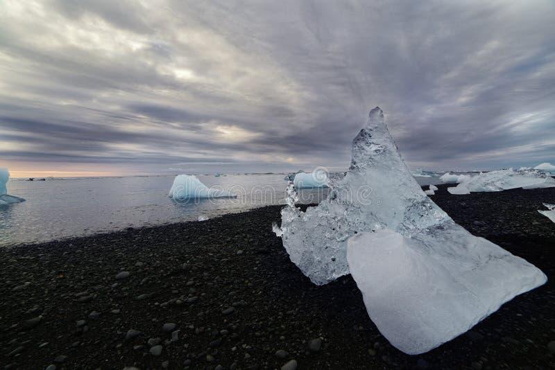 Masas de hielo flotante de hielo en la orilla y flotación en el agua en la puesta del sol islandia foto de archivo