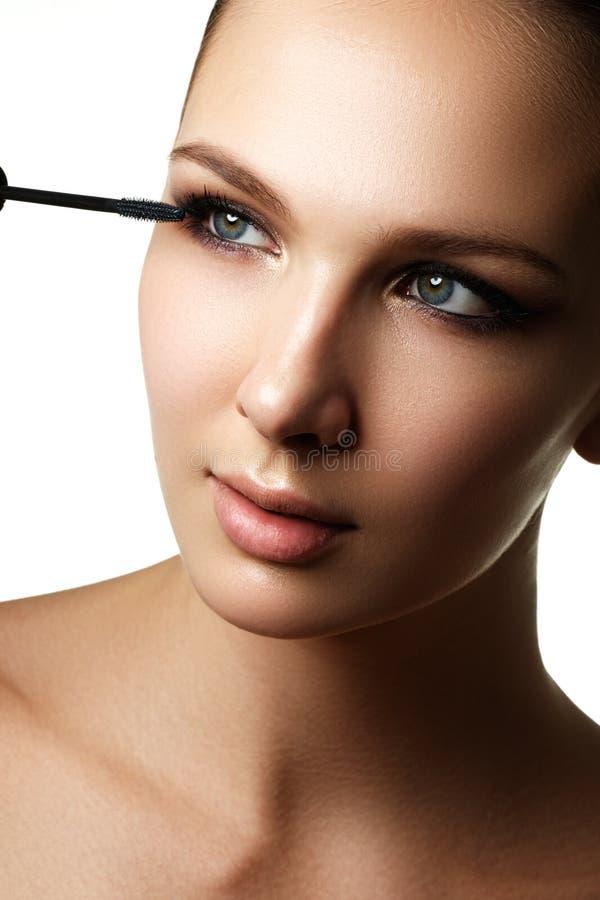 Mascara che applica primo piano, sferze lunghe Spazzola della mascara eyelashes fotografie stock libere da diritti