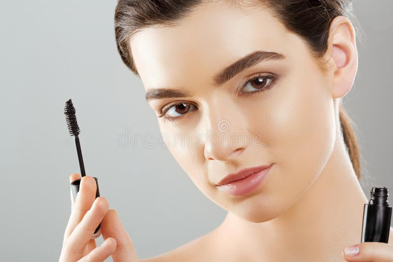 Mascara Closeup Of A Beautiful Young Woman A Face With A Beauty Makeup, Fresh Soft Skin Applying Mascara With Cosmetic Brush. Make. Up And Cosmetics Concept royalty free stock images
