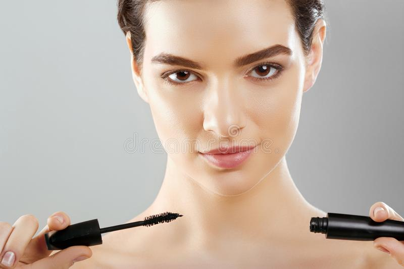 Mascara Closeup Of A Beautiful Young Woman A Face With A Beauty Makeup, Fresh Soft Skin Applying Mascara With Cosmetic Brush. Make. Up And Cosmetics Concept royalty free stock photo
