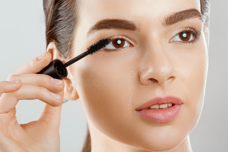 Mascara Closeup Of A Beautiful Young Woman A Face With A Beauty Makeup, Fresh Soft Skin Applying Mascara With Cosmetic Brush. royalty free stock photography