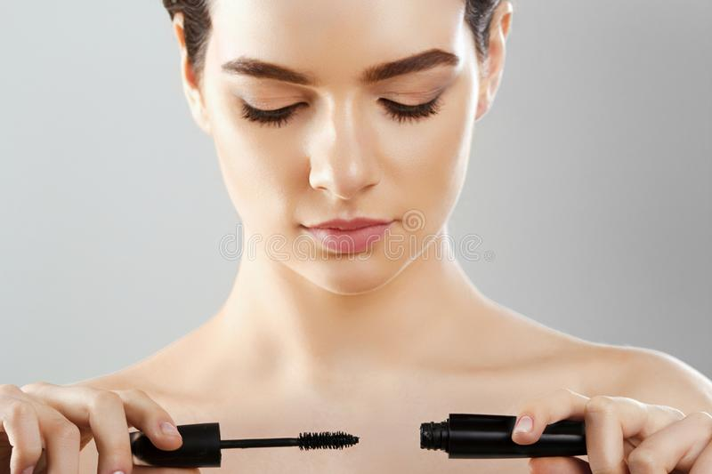 Mascara Closeup Of A Beautiful Young Woman A Face With A Beauty Makeup, Fresh Soft Skin Applying Mascara With Cosmetic Brush. Make. Up And Cosmetics Concept stock images