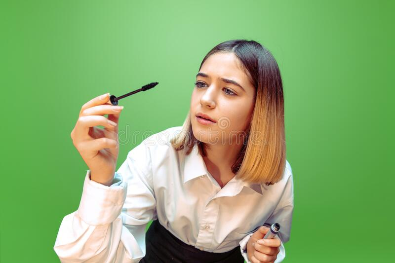 Little girl dreaming about future profession of makeup and hairstyle artist stock photography