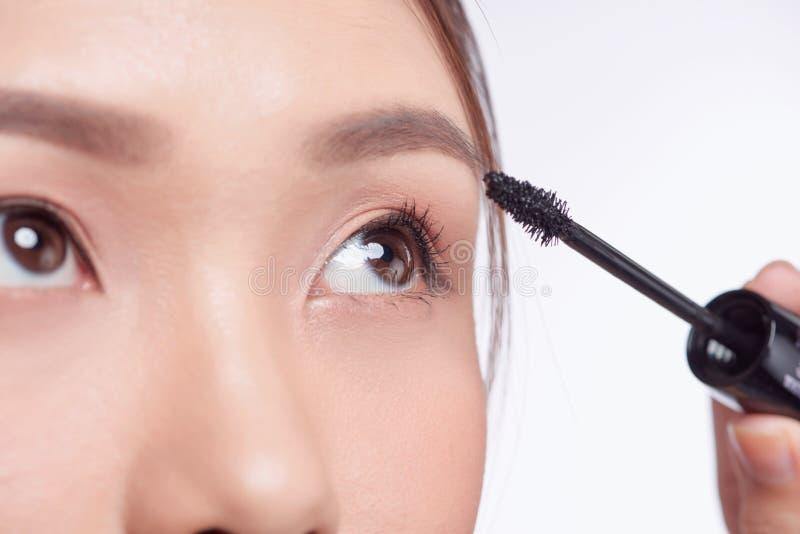 Mascara woman putting makeup on eyes. Asian female model face closeup with eye brush on eyelashes.  royalty free stock images