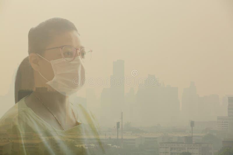Mascarilla de la mujer que lleva debido a la contaminación atmosférica en la Bangkok imagen de archivo