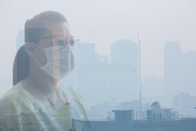 Mascarilla de la mujer que lleva debido a la contaminación atmosférica en la Bangkok fotografía de archivo