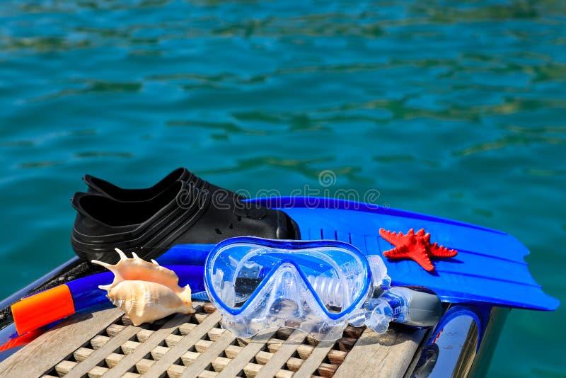 Maschera, alette, macchina fotografica subacquea, conchiglie sui precedenti del mare fotografia stock