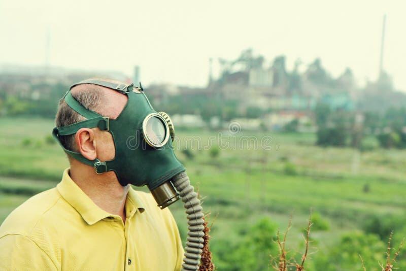 Maschera antigas d'uso della persona sul fondo industriale della fabbrica fotografia stock libera da diritti