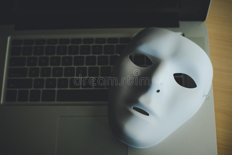 Maschera bianca disposta sul computer portatile - frode di concetto di online sociale fotografia stock libera da diritti