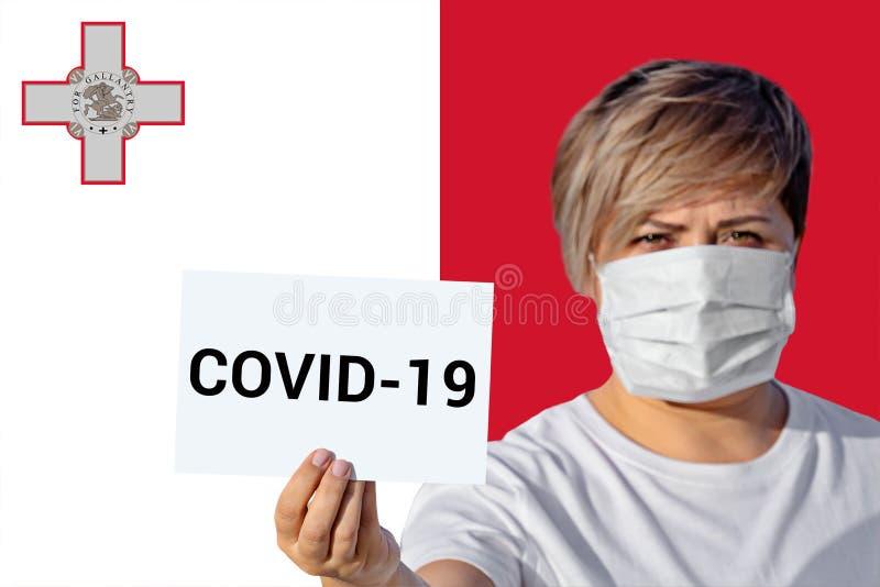 Maschera con maschera di viso con iscrizione COVID-19 contro bandiera maltese fotografia stock libera da diritti