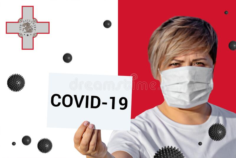 Maschera con maschera di viso con iscrizione COVID-19 contro bandiera maltese immagine stock libera da diritti