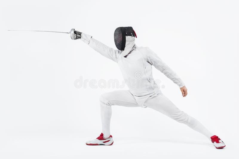 Maschera d'uso del giovane atleta dello schermitore e costume di recinzione bianco tenuta della spada Isolato su priorità bassa b fotografia stock libera da diritti