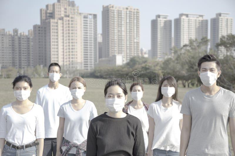 Maschera d'uso della bocca del giovane gruppo contro inquinamento atmosferico in città fotografie stock