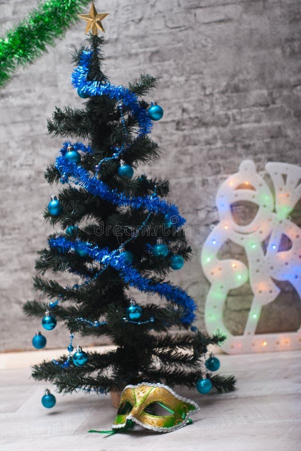 Maschera di carnevale sotto l'albero di Natale fotografia stock libera da diritti