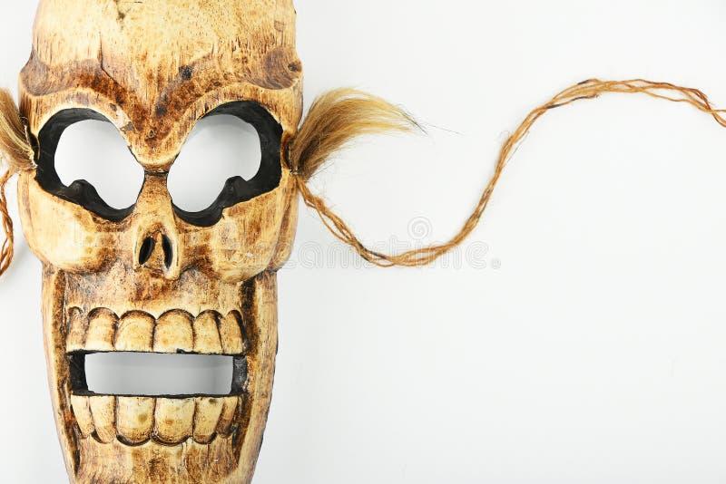 Maschera di morte scolpita di legno del cranio su bianco immagini stock libere da diritti