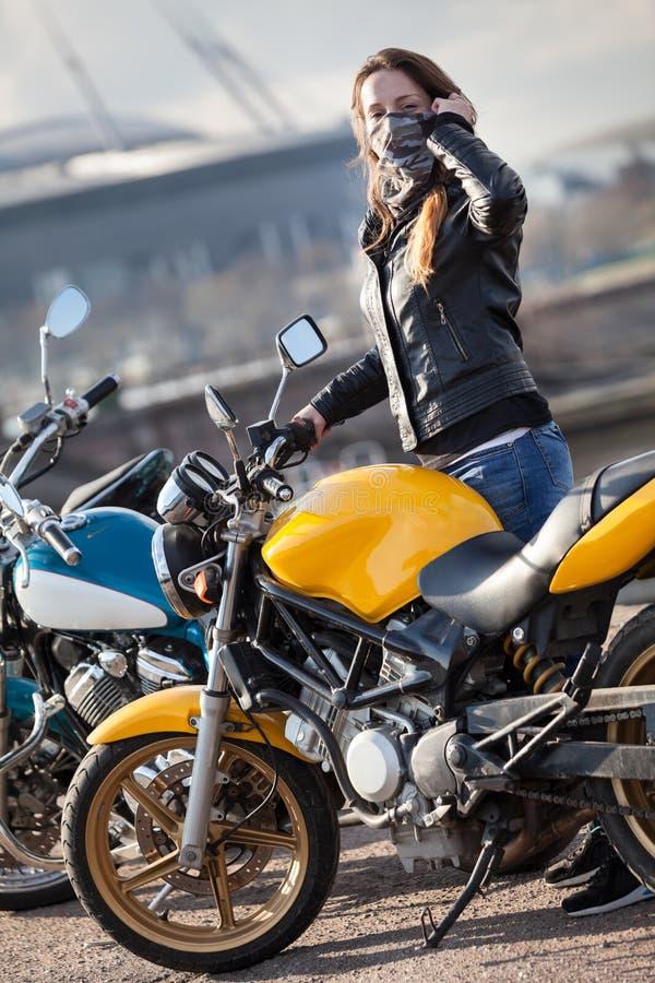 Maschera di protezione d'uso del collo del motociclista della giovane donna che sta accanto alla bici della via all'aperto fotografie stock