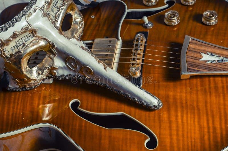 Maschera e chitarra elettrica veneziane fotografia stock libera da diritti