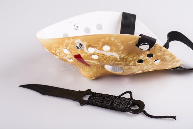 Maschera e coltello dell'assassino su bianco immagini stock