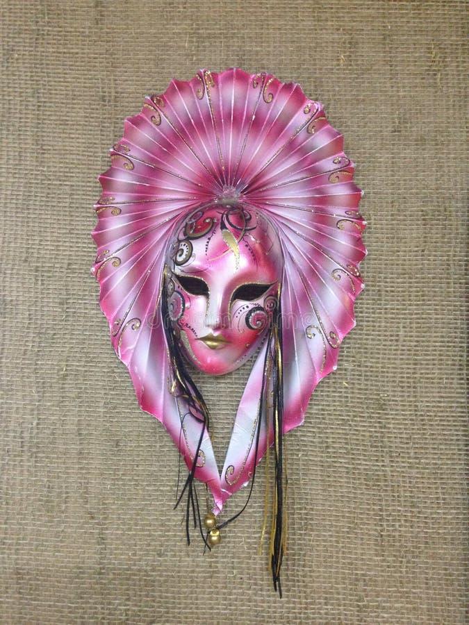 Maschera esotica di travestimento sulla tela della tela da imballaggio Maschera rosa con un grande fan sui modelli dell'bianco-ne immagine stock