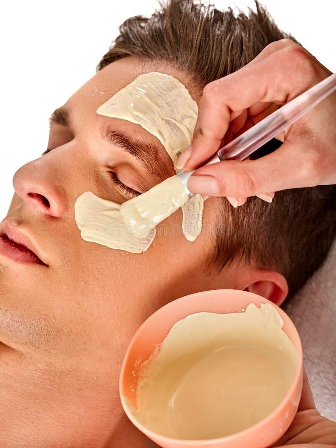 Maschera facciale del fango dell'uomo nel salone della stazione termale Massaggio di fronte fotografia stock