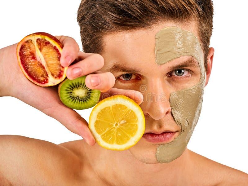 Maschera facciale dell'uomo dai frutti e dall'argilla Fango del fronte applicato immagini stock libere da diritti