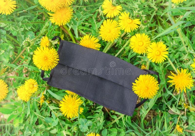 Maschera medica giace sui fiori, primo piano immagini stock