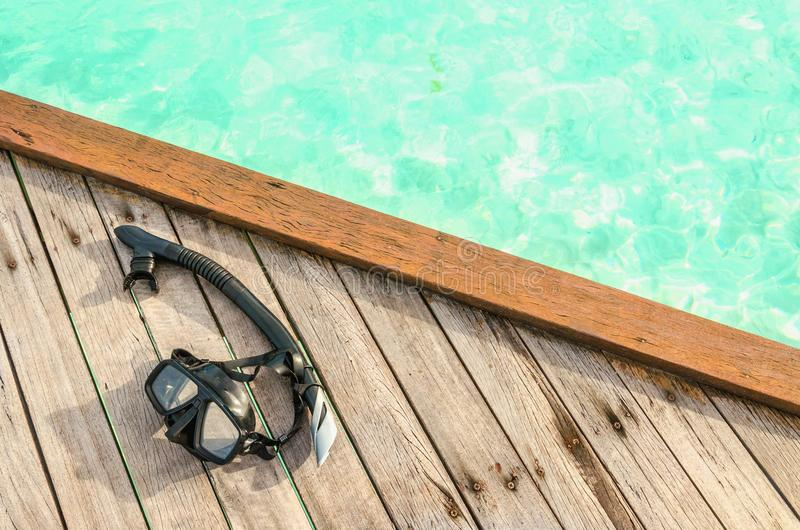 Maschera nera per immergersi su un punto di legno contro acqua azzurrata fotografia stock libera da diritti