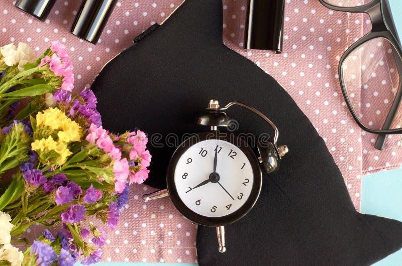 Maschera per il sonno con orologio, fiori, mascara e pomodoro sulla composizione di fondo blu immagini stock