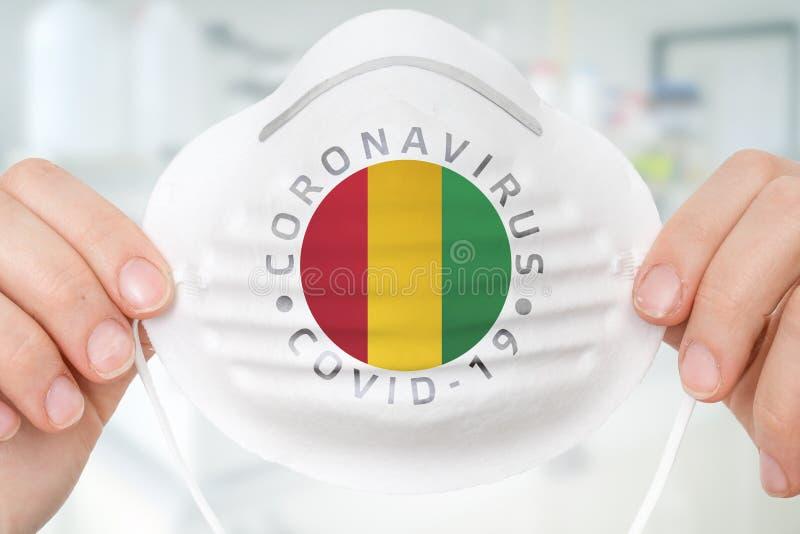 Maschera respiratrice con bandiera della Guinea - Conce Coronavirus COVID-19 immagini stock libere da diritti