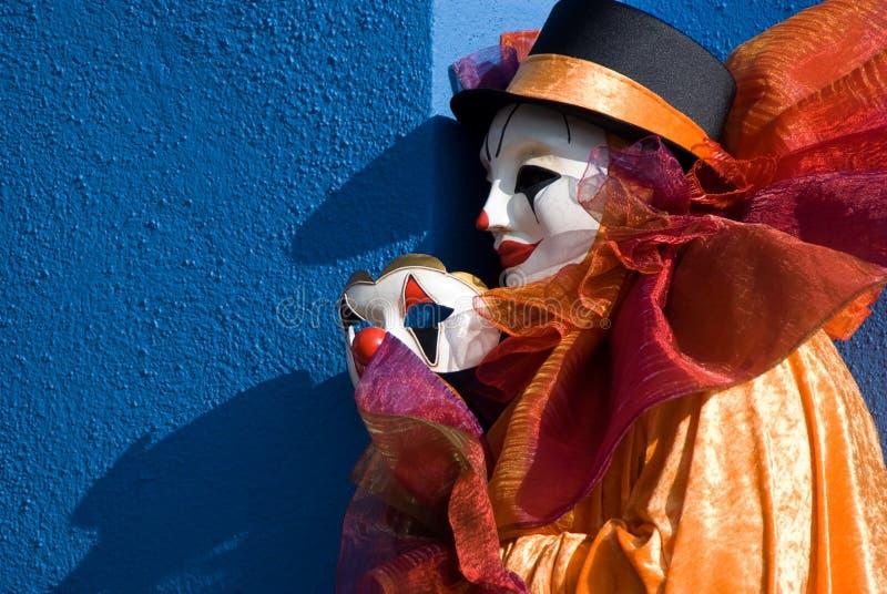 Mascherina della holding del pagliaccio davanti alla parete blu fotografie stock libere da diritti
