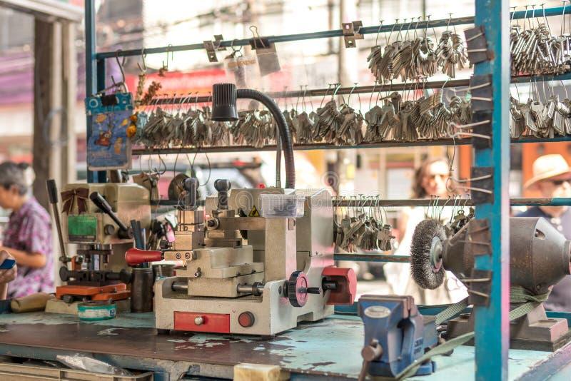Maschinelle Herstellung von doppelten Metallschlüsseln für Türen auf der Straße von Bangkok lizenzfreie stockfotos