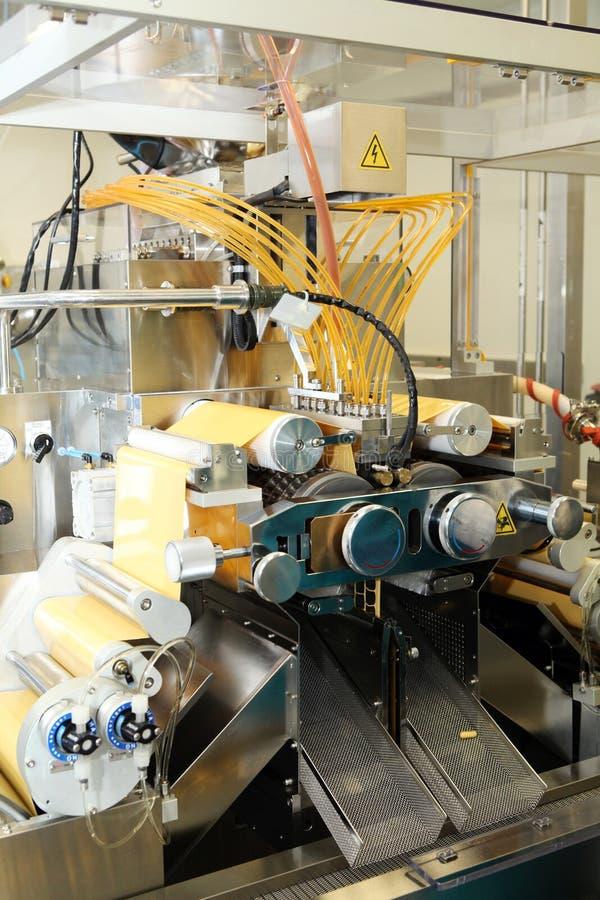 Maschinenfertigung von Gelatinekapseln Bestätigung des Maschinenmannes Produktion von Kapseln für Tabletten lizenzfreie stockfotografie