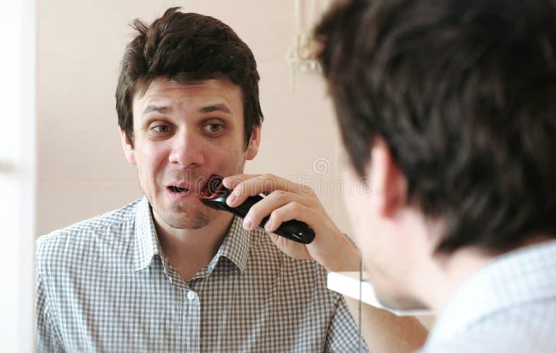 Maschinenrasur-Gesichtshaar Junge Trockenrasur des gutaussehenden Mannes mit elektrischem Trimmer stockbild