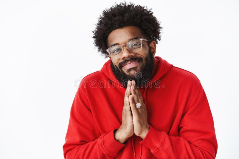 Maschio afroamericano amichevole di aspetto freddo e spensierato con la barba in vetri che fanno sguardo di angelo come tenersi p immagine stock