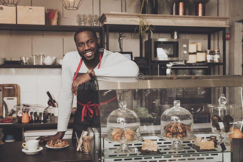Maschio afroamericano sorridente di barista sul lavoro fotografia stock libera da diritti